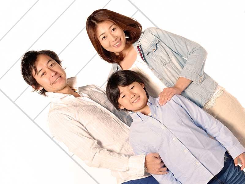両親と背比べをしている男の子