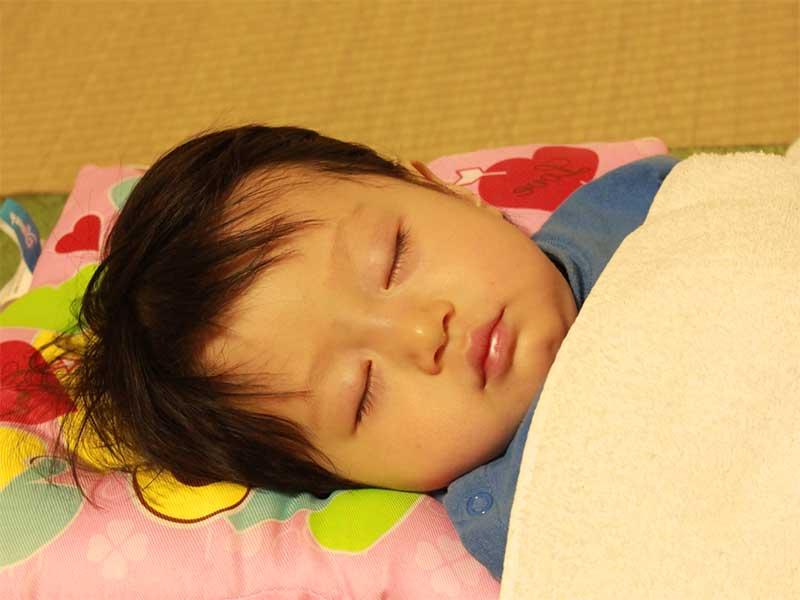 布団でぐっすり寝ている子供