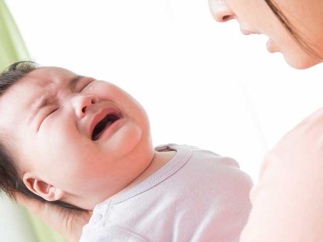 泣く赤ちゃんをあやす母親