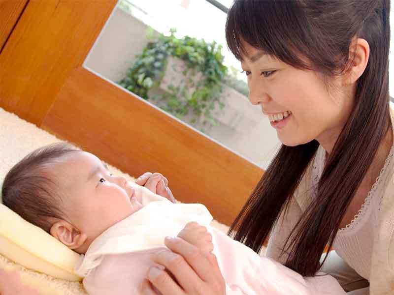 新生児に顔を近づけて歌っている母親