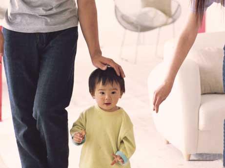 父親に頭を撫でられている小さい子供