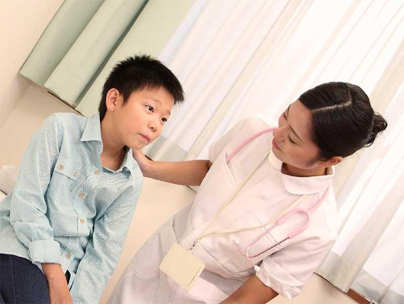 病院で看護師と一緒にいる男の子