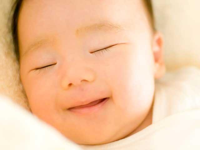 寝ながら微笑む赤ちゃん