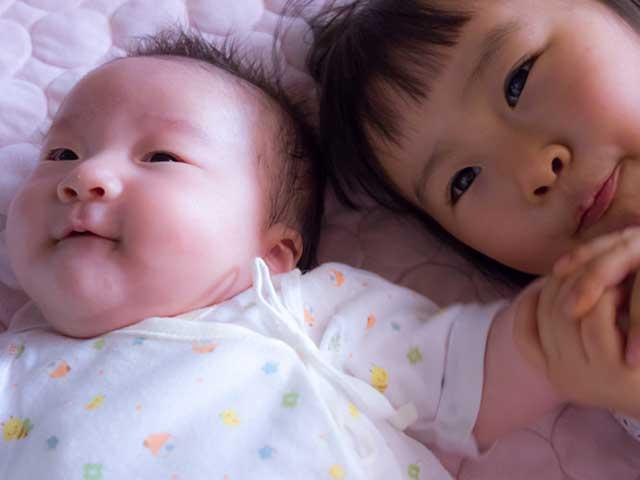 赤ちゃんの傍に一緒に居るお姉さん