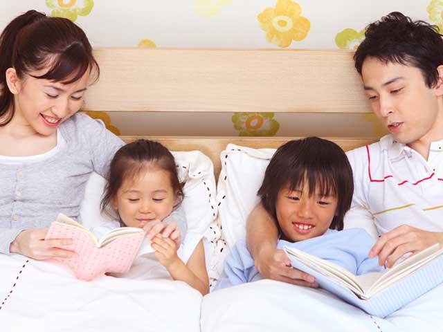 子供に本を読んであげる両親