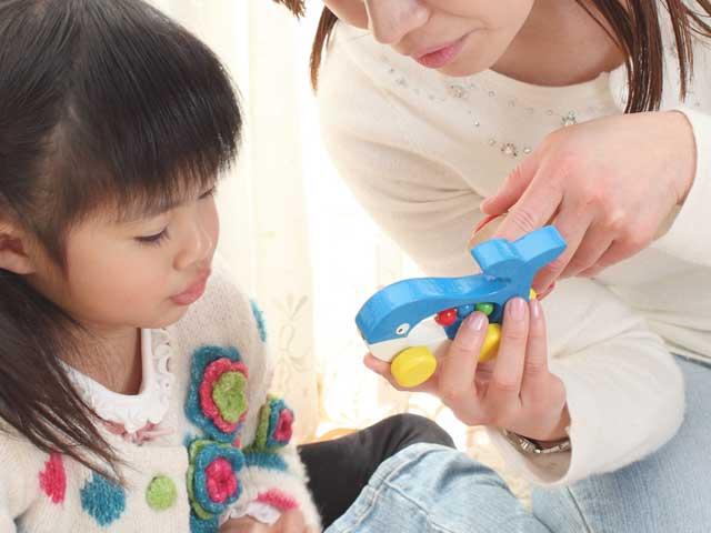 子供の玩具を取り上げて説明する母親