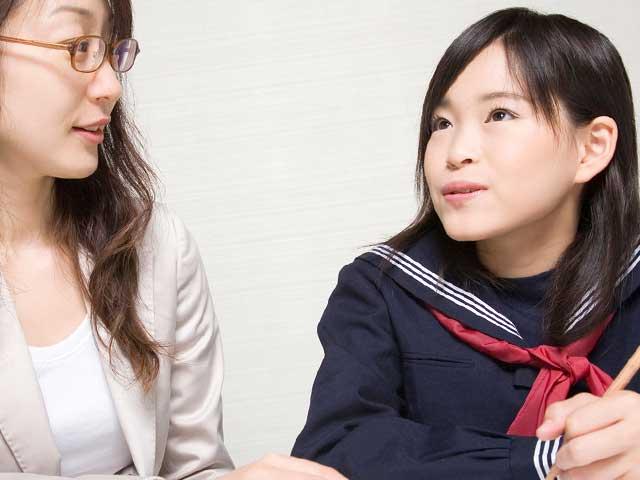 制服姿の女子中学生の話を聞く母親