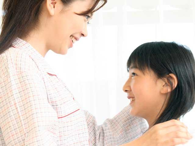 子供の肩に手を置く母親