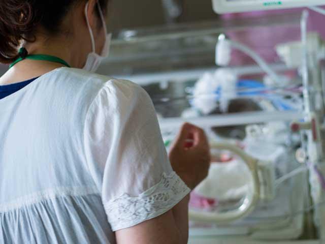 新生児室で赤ちゃんを見る女性