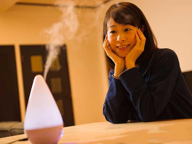 加湿器の前で水蒸気を見つめる女性