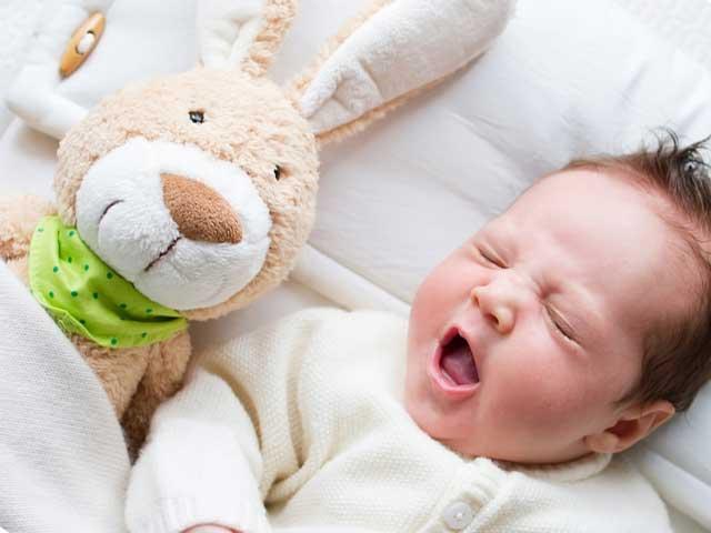 ぬいぐるみと一緒に寝る赤ちゃん