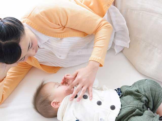 赤ちゃんに添い寝する母親