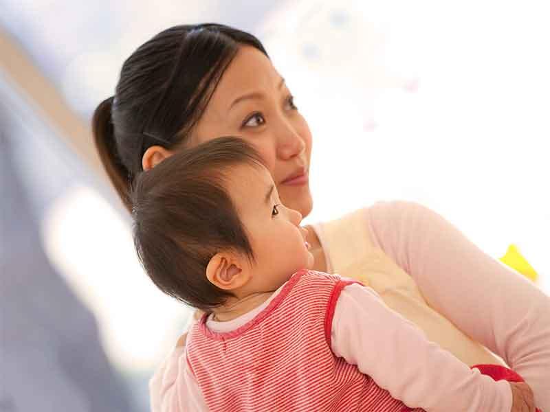 0歳の女の子を抱っこしている女の保育士