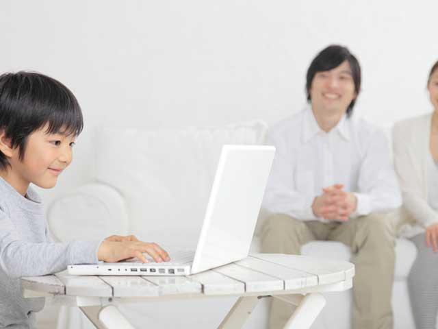 パソコンを操作する子供を見守る親