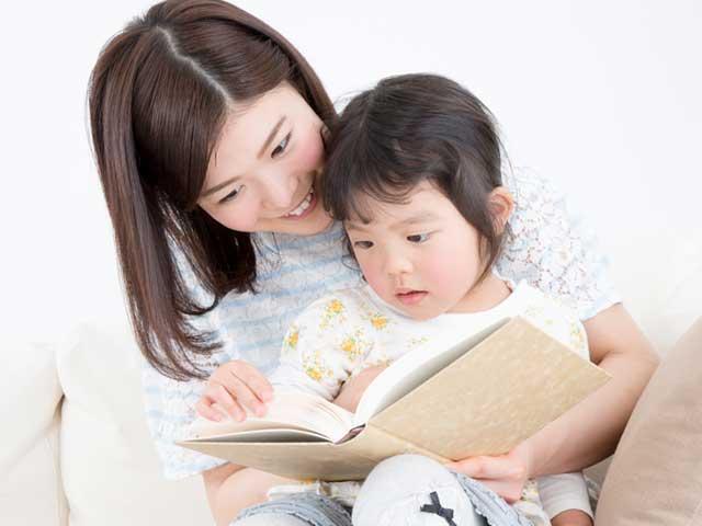 膝に座らせた子供に絵本を読む母親