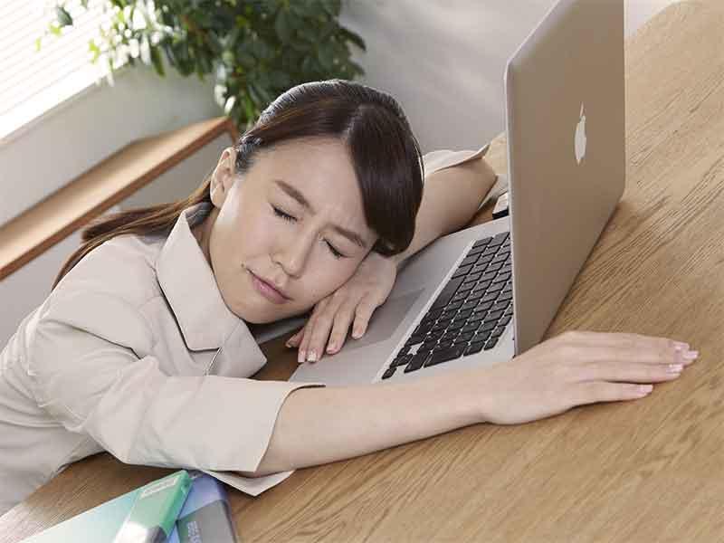 仕事が忙しくて会社のパソコンの前で突っ伏している女性