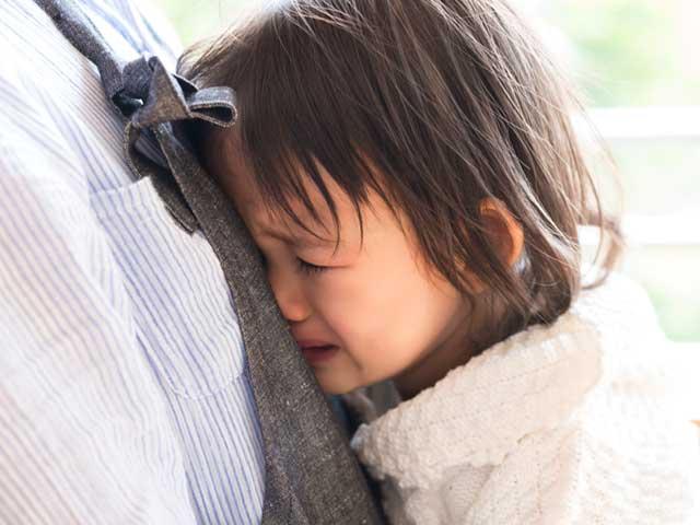 母親にしがみついて泣く子供