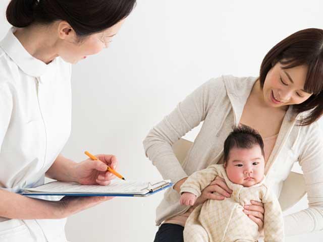 保健師さんの問診をうける母親