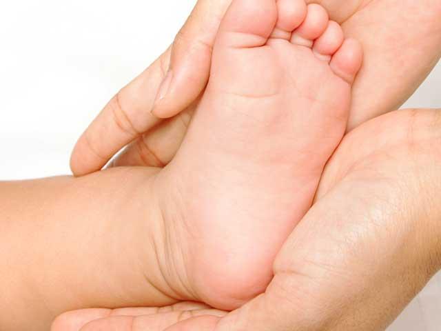新生児の足を持って甲を触る