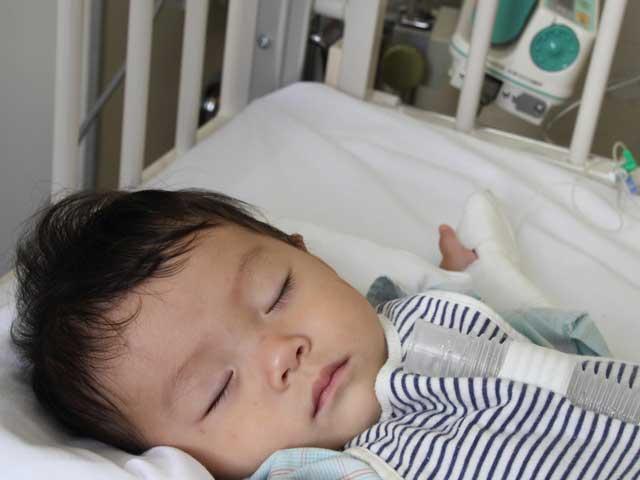 病院のベッドで眠る幼児