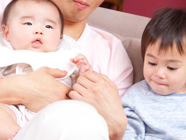 抱っこされる赤ちゃんと隣に座るお兄ちゃん