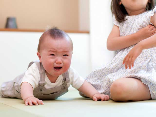 お姉ちゃんの傍で泣く赤ちゃん