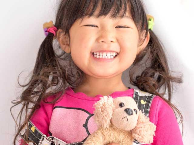 ぬいぐるみを持って笑顔の幼児