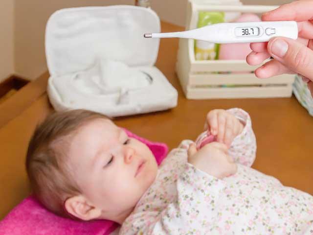 赤ちゃんと体温計を持つ親の手