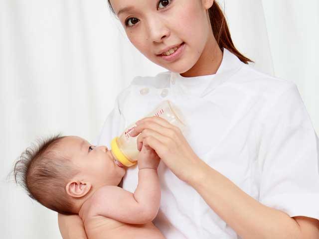 看護師にミルクを飲ませてもらう赤ちゃん