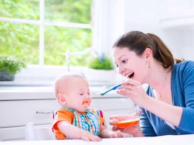 ニンジン離乳食を赤ちゃんに食べさせる外人女性