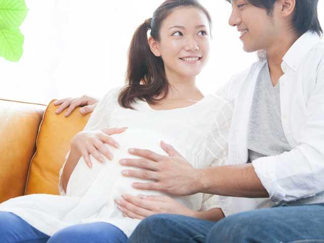 妊婦の妻のお腹に手を当てる夫