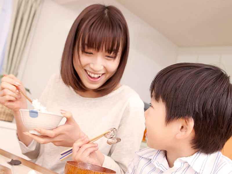 ご飯を食べて笑顔の男の子と母親