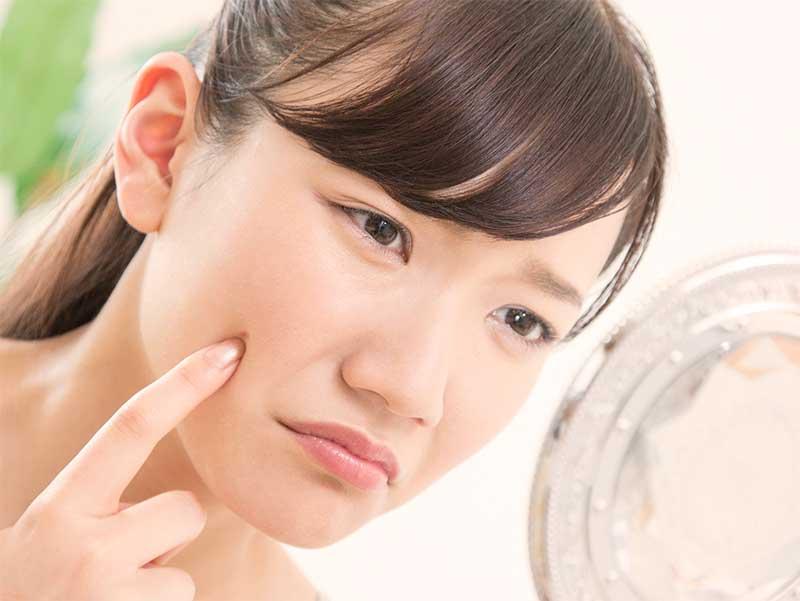 鏡で頬にできたニキビを確認している若い女性