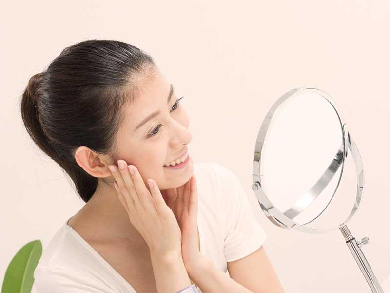 鏡で自分の顔を見て笑顔の女性