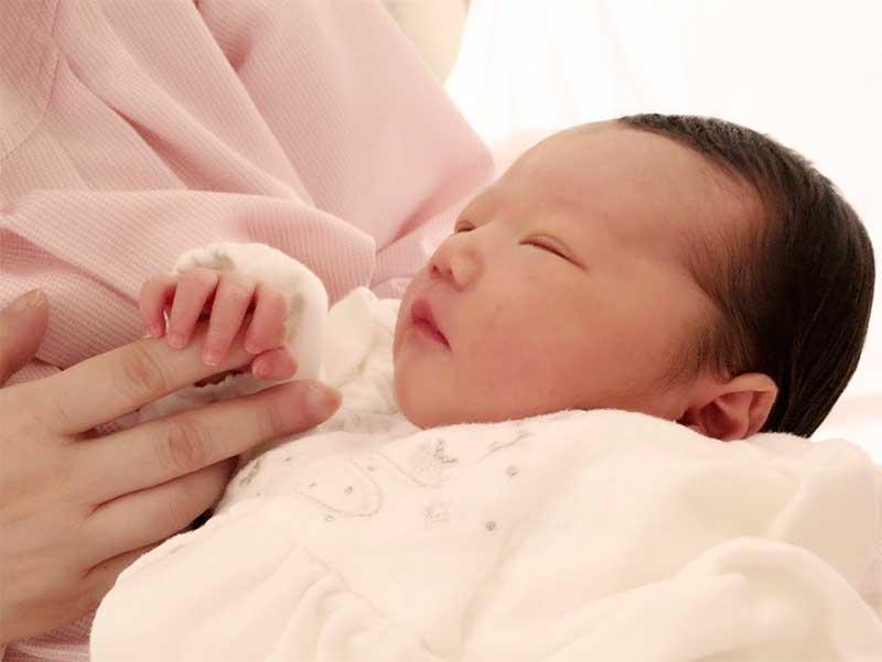 寝ている新生児の手を触っている母親