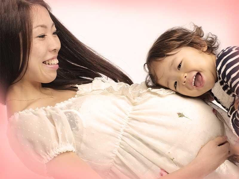 二人目を妊娠している母親のおなかに耳をあてている上の子供