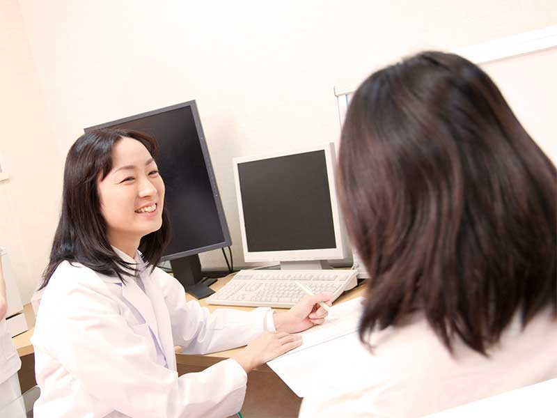 産婦人科で医師に相談する妊娠している女性