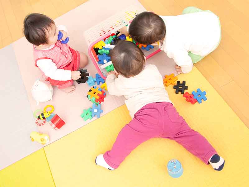 保育園で遊んでいる3人の赤ちゃん