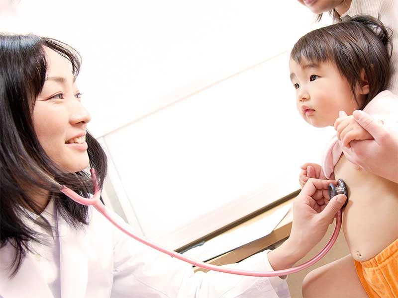 病院で医者からお腹に聴診器をあてられてる幼児