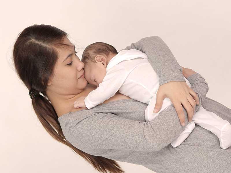 新生児を抱っこしている母親