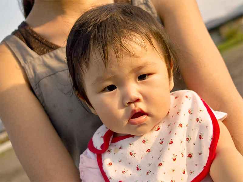 母親に抱っこされたスタイをつけてる赤ちゃん
