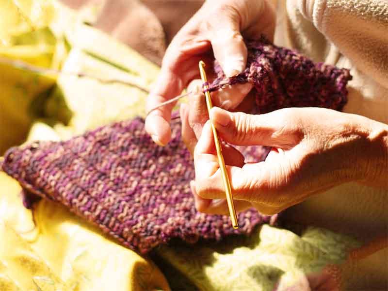 毛糸のおくるみを編んでいる女性