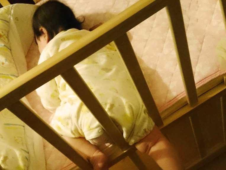 ベビーベッドから足を出した状態で寝てる赤ちゃん