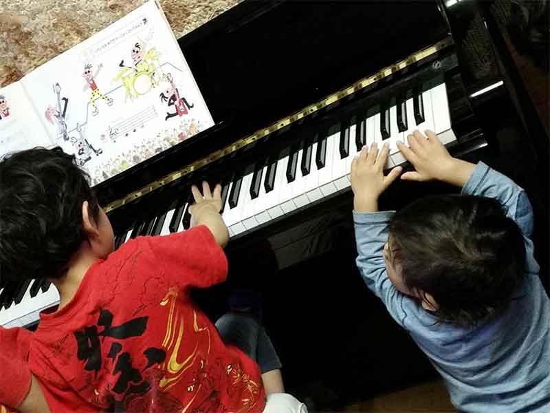 ピアノを弾いてるお兄ちゃんを見てピアノに触ってる2歳の子供