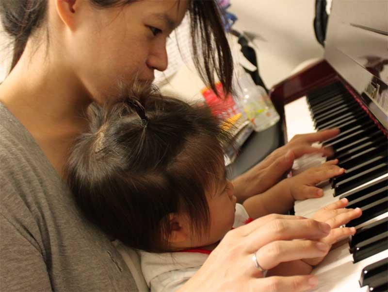 子供と一緒にピアノを弾いているママ