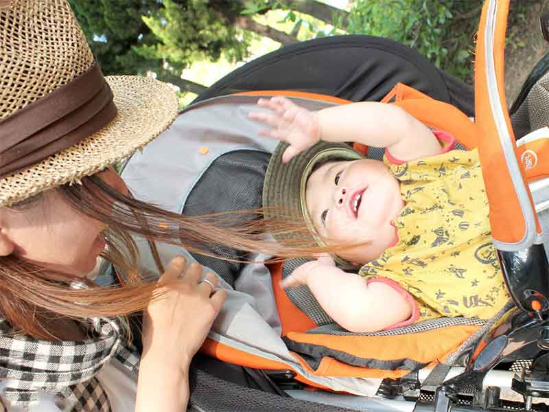 太陽の陽の下でベビーカーに乗って散歩してる赤ちゃんとママ