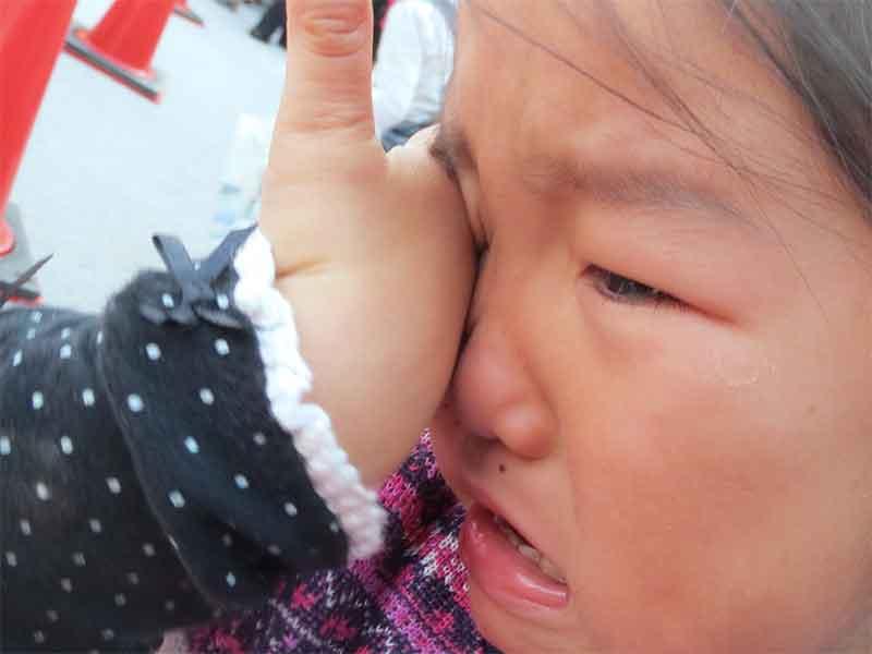 口をぶつけて泣いている女の子