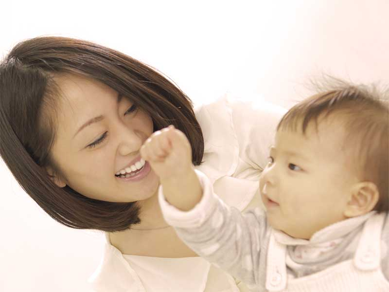 赤ちゃんのおしゃべりを笑顔で見てるママ