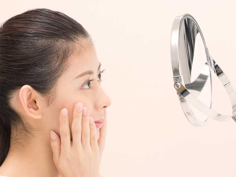 鏡で顔の肌荒れをチェックしる女性