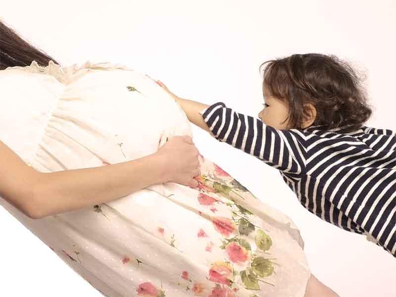 妊娠しているママのお腹を触る女の子